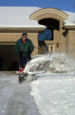 A man using a snowblower after a storm. 12MP camera, Model released. Фото со стока