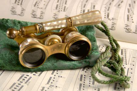 Antike Oper Gläser stehen auf einer tattered Samtbeutel- und -blattmusik still. Flacher DOF, Focus=camera rechtes Objektiv. Kamera 12MP.