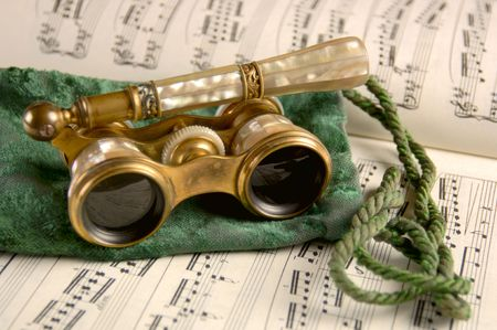 Antique opera glasses rest on a tattered velvet pouch and sheet music. Shallow DOF, Focus=camera right lens. 12MP camera. Foto de archivo
