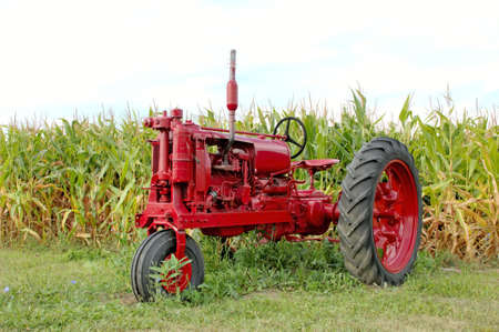 Antique red tractor in front of a corn field. Michigan, U.S.A.  12MP camera.