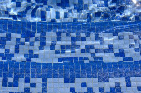 Three tiled swimming pool steps underwater with light reflections. Focus = the middle step. 12MP camera. Фото со стока