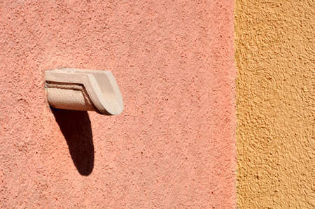Sunny Mexican stucco on a balcony with a clay drain. The balcony and wall are at right angles. 12MP camera.