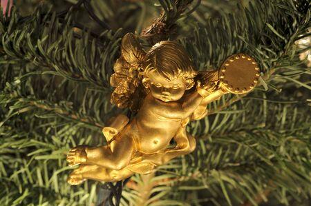 Hanging angel (cherub) ornament in a Christmas tree. Macro.