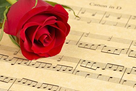 A red rose bud rests on sheet music