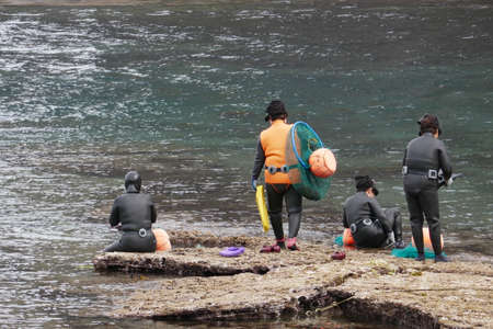 Jeju Island, South Korea - April 16, 2018 : Haenyo divers prepare to dive to harvest seafood. They can hold their breath for 2 minutes and go 20 meters deep.