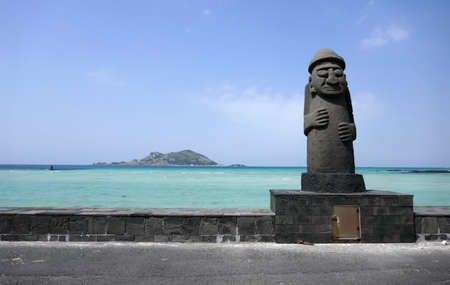 Jeju Island, South Korea - April 17, 2018 : Dol hareubang stone statue in front of a turquoise sea with volcanic island.