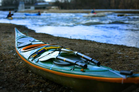 A kayak sits on the shore of a river