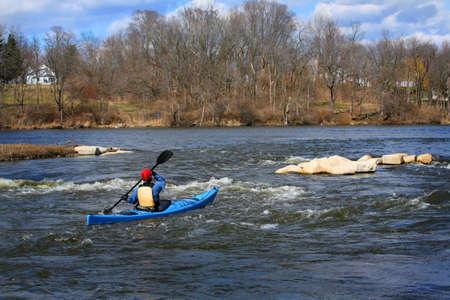 A kayaker paddles down a river Editöryel