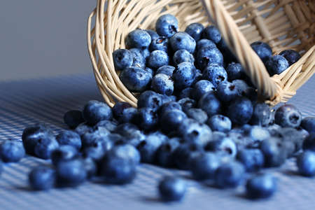 blueberries spilling out of a wicker basket photo