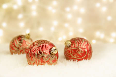 Red and gold Christmas ornaments on white rug with gold background and lights photo