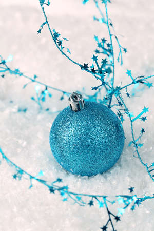 Blue glitter Christmas ornament on snow