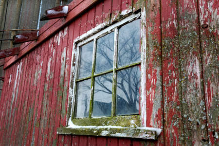 An old red barn window with peeling paint and moss