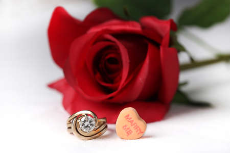 Womans wedding ring with Valentines Day candy heart and rose