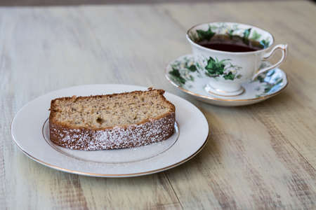 banana bread: Cup of tea in antique bone china teacup with banana bread on white plate