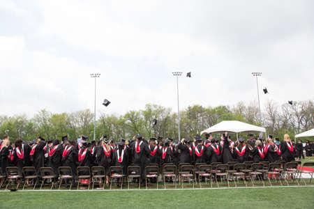 toss: college graduates toss caps in the air