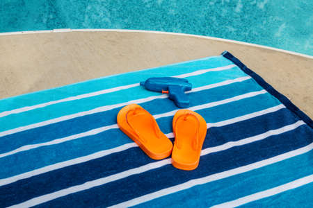 Orange flip flops on blue striped beach towel photo