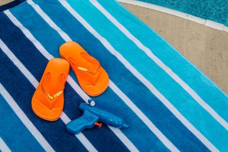 Orange flip flops and squirt gun on beach towel next to pool photo