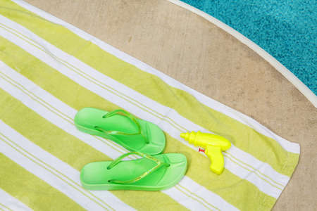 Green flip flops and squirt gun next to a pool photo