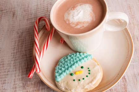 Home made cookies de bonhomme de neige, des cannes de bonbons et chocolat chaud sur une plaque photo