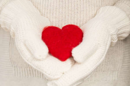 Red Valentines Day heart in hands with mittens 写真素材