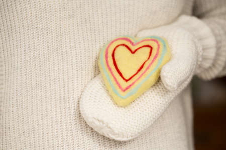 Handmade Valentines Day heart in hand with knit mitten Фото со стока