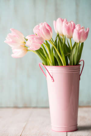 Pink and white pastel Tulips in a pink bucket vase photo