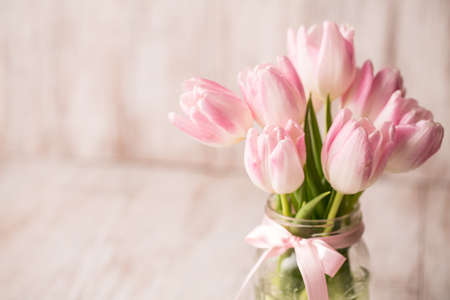 Pink and white Tulips in glass jar vase with pink bow photo