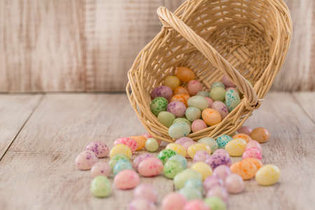Colorful pastel Easter Egg candy spilling out of wicker basket photo