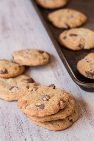 cookie sheet: chocolate chip cookies stacked and in row on cookie sheet Stock Photo