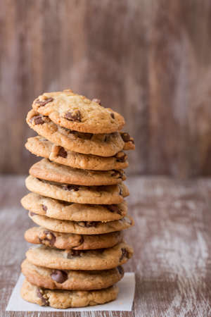 A tall stack of chocolate chip cookies for dessert photo