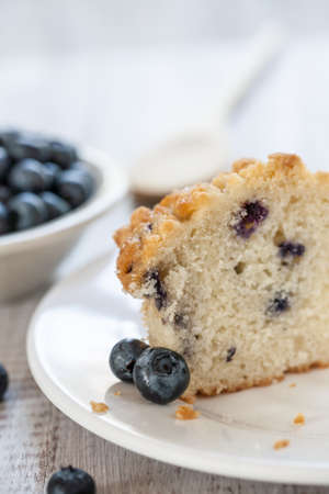 Blueberry muffin cut in half with bowl of blueberries and wooden spoon photo