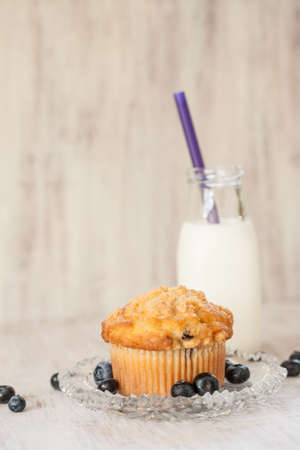 Blueberry muffin breakfast on plate with glass jug of milk
