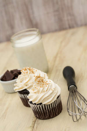 Chocolate cupcakes with white vanilla frosting with glass of milk and pieces of chocolate and wisk vertical