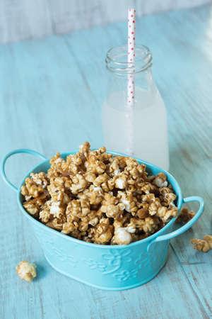 Blue tin with caramel popcorn and lemon soda pop with straw Imagens