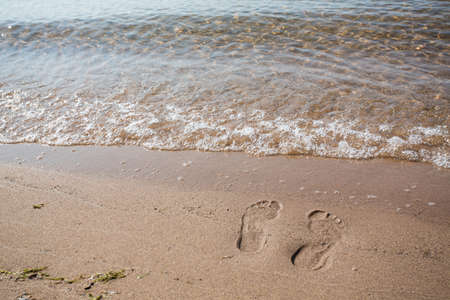 Footprints in the sand of beach on Lake Michigan with wave Imagens
