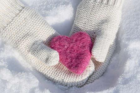 Mittens with Valentines Day love heart in the snow in winter