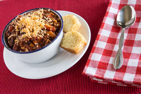 Bowl of warm chili winter comfort food with corn bread muffin
