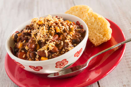 Bowl of warm chili winter comfort food dinner with corn bread muffin on red plate Imagens