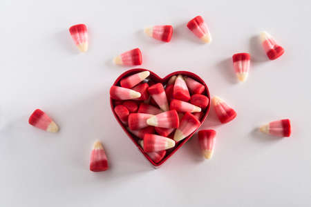 scattered in heart shaped: Valentines Day candy corn in heart shaped cookie cutter with candy scattered