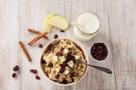 petit dejeuner: C�r�ales de petit d�jeuner flocons d'avoine avec canneberges et les pommes et les b�tons de cannelle et le lait Banque d'images