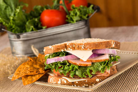 swiss cheese: Ham turkey lettuce swiss cheese and onion sandwich with chips Stock Photo