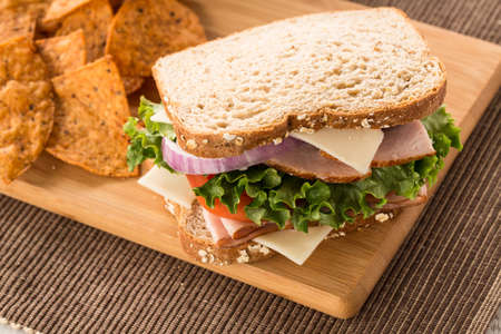 swiss cheese: Turkey Ham and Swiss cheese sandwich on wood cutting board with chips Stock Photo