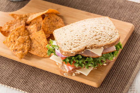 swiss cheese: Ham turkey and swiss cheese and onion sandwich with tomato and lettuce and chips