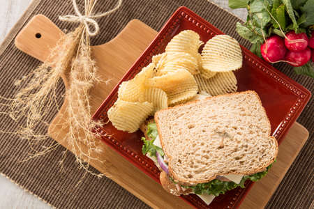swiss cheese: Ham turkey and swiss cheese sandwich with potato chips and radishes from above Stock Photo