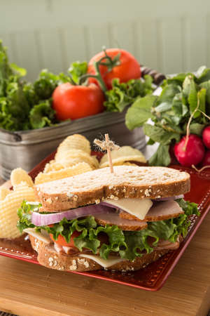 swiss cheese: Lunch sandwich with turkey ham and swiss cheese with potato chips and vegetables