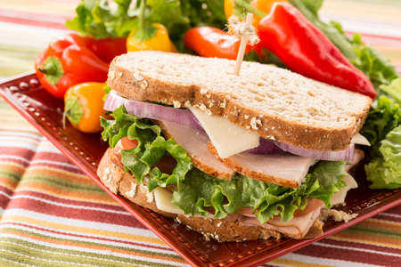 Healthy lunch food sandwich with turkey and ham on a plate with sweet peppers and lettuce photo
