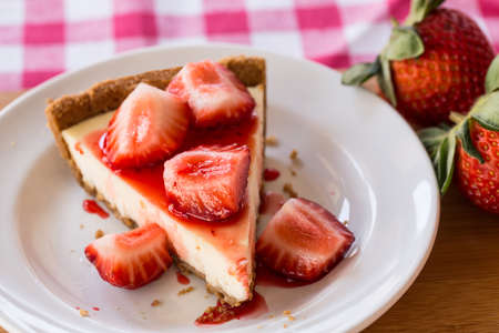 cut up: Photo of slice of cheesecake with fresh cut up strawberries on white plate