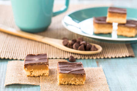 Millionaire bars caramel and chocolate shortbread cookie candy bars with chocolate chips and coffee cup