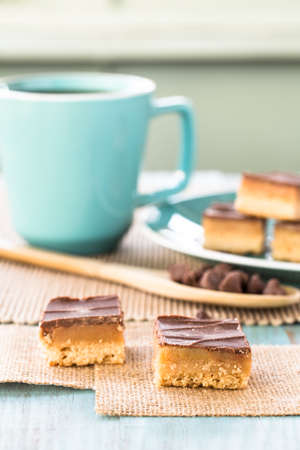 vertical bars: Chocolate and caramel candy cookies Millionaire Bars with wood spoon and chocolate chips vertical