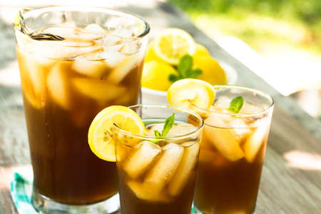Iced tea summer drink with lemons on picnic table